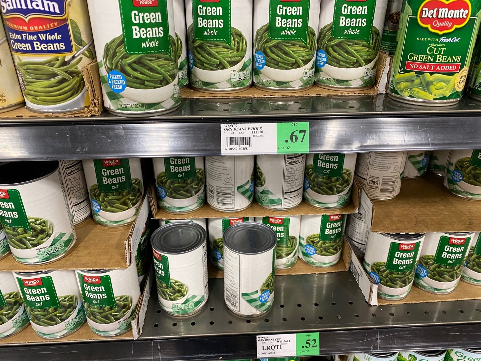 A picture of canned green beans on the shelf of a grocery store.